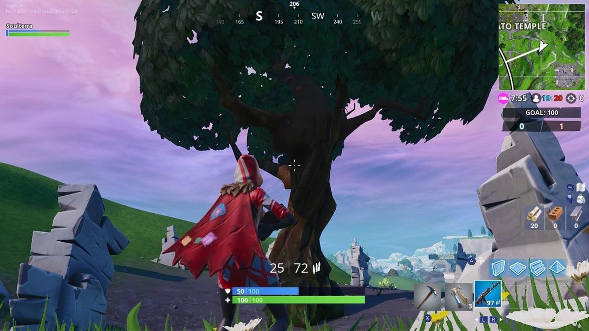 Fortnite Saison 7 semaine 5 défis recherche entre un rocher géant homme couronné tomate et arbre encerclé.