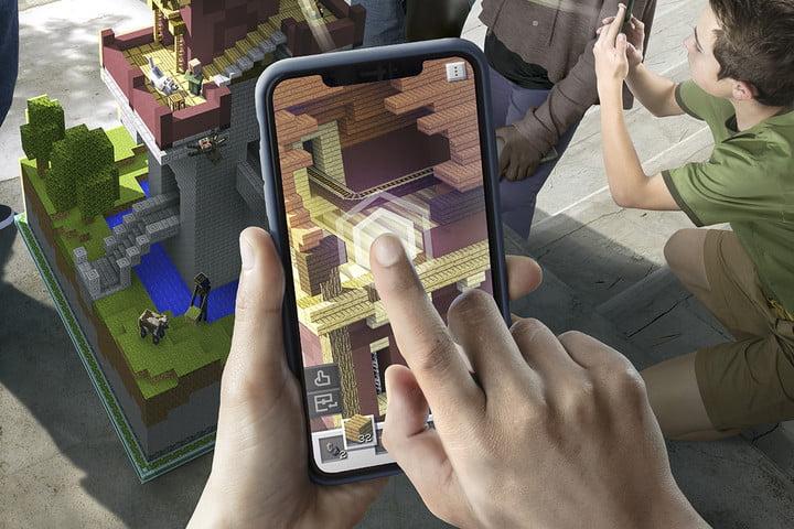 Joueur plaçant un bloc dans l'application sur l'écran du téléphone | Minecraft Earth Key Art